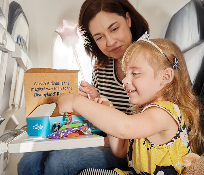A little girl opening a snack box with her mom beside her